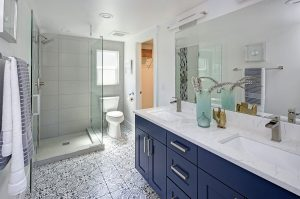 Modern bathroom interior with blue double vanity and glass shower.