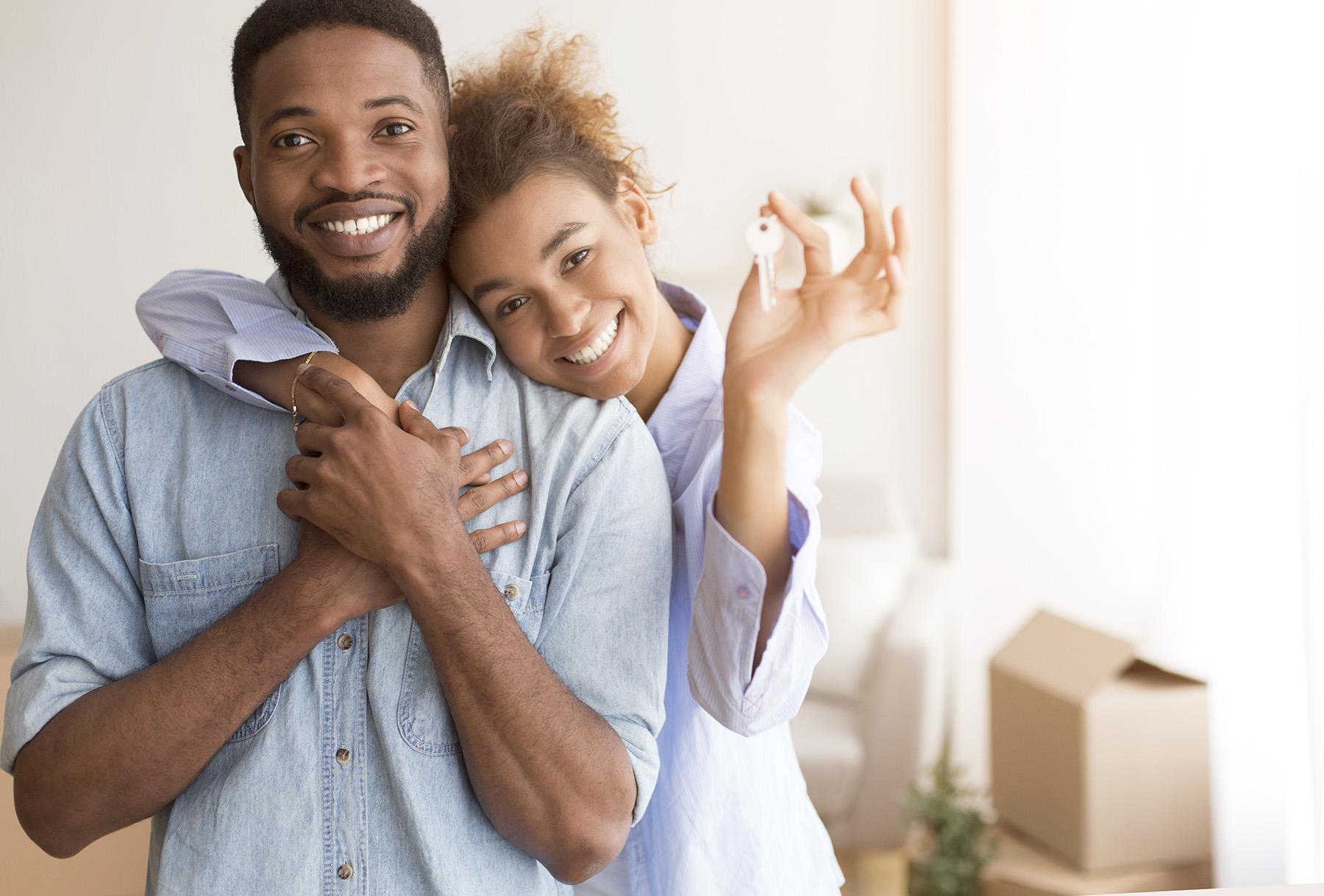 Moving Concept. Cheerful Couple Holding New Home Key Hugging Standing In Own House After Relocation. Selective Focus, Free Space